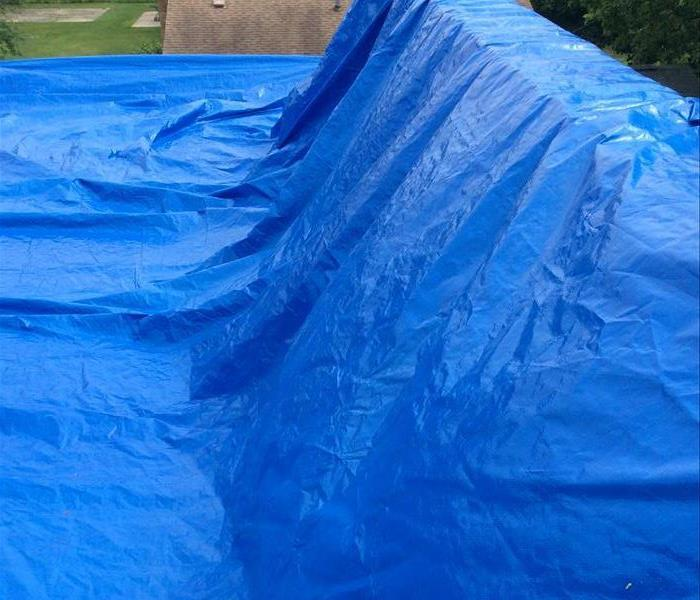 Commercial Building roof with large blue tarps protecting compromised roof area from further damage