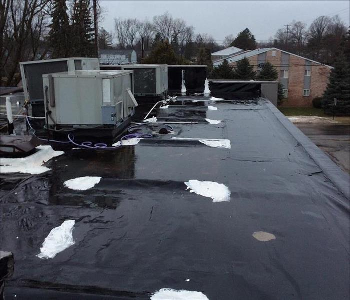 Large amounts of rain water and heavy melting snow pools up on the roof of a commercial building