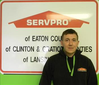 male employee with blonde hair smiling in front of SERVPRO sign
