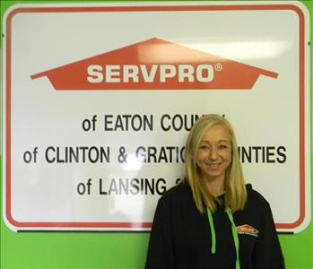 Blonde Female smiling in front of SERVPRO sign