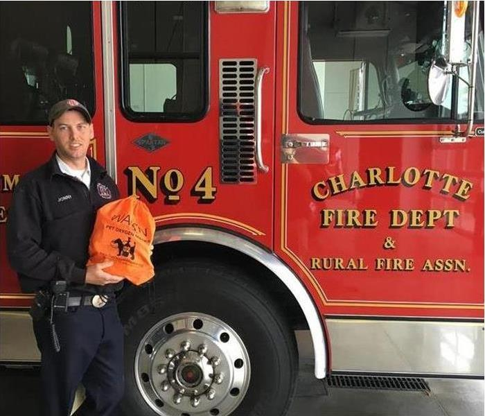 Fireman holds orange bag with pet oxygen supplies insdie. standing in front of fire truck