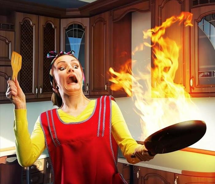 Surprised woman in home kitchen wearing a red apron over a yellow shirt, holding wooden spoon in one hand and a skillet with