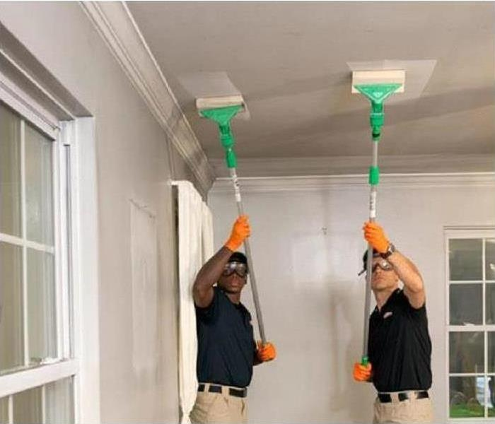 Servpro employees use a dry chem sponge to clean soot from ceiling