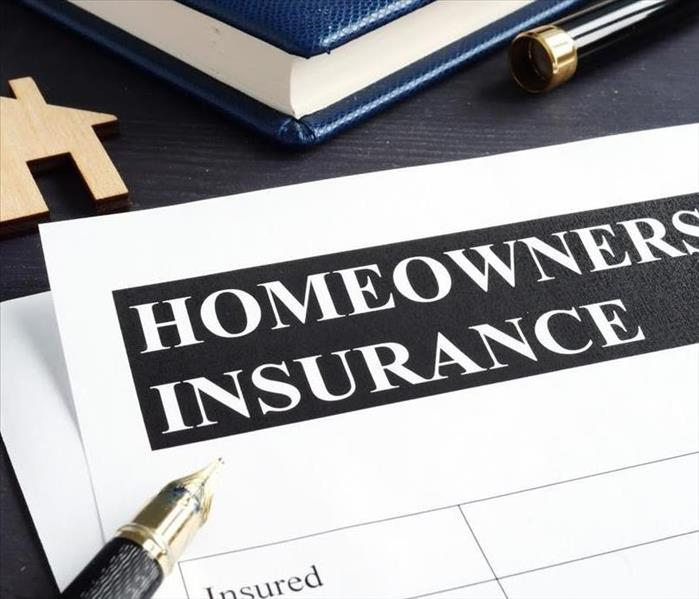 Black pen laying on table on top of homeowner's insurance paper checklist