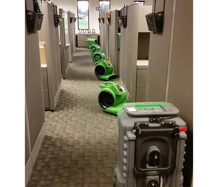 Air movers and dehumidifiers drying out employee workspaces