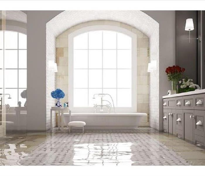 Large bathroom with white tile floor and gray cabinets submerged in flooding water